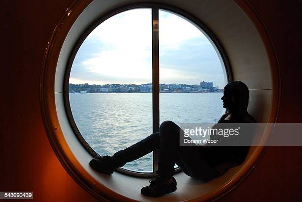 The Atlantic Ocean is seen on the shore of Staten Island New York through a large round window of a cruise ship with a silhouette of a young woman...