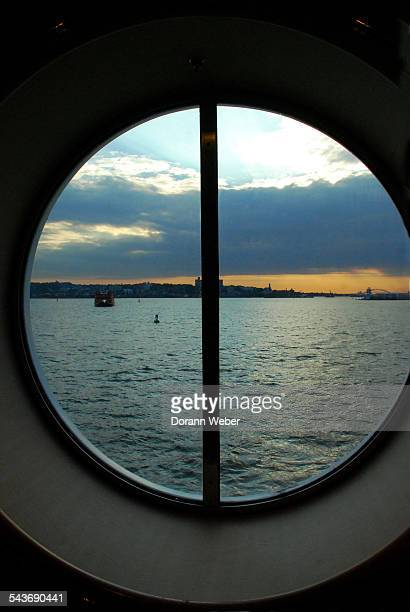 The Atlantic Ocean is seen on the shore of Staten Island New York through a large round window of a cruise ship