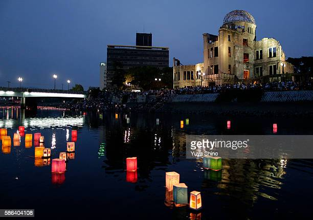 The Atomic Bomb Dome is seen behind floating candle lit paper lanterns on the river during 71st anniversary activities commemorating the atomic...