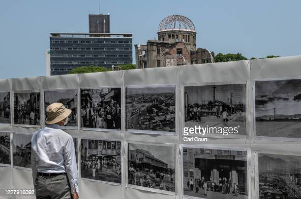 The Atomic Bomb Dome looms in the background as a man views an exhibition of photographs of Hiroshima after it was destroyed by the atomic bomb...