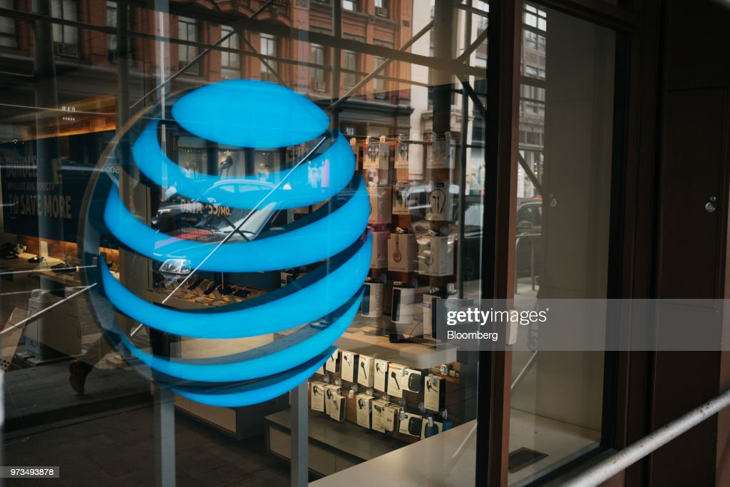 The AT&T Inc. logo is displayed outside a store in New York, U.S., on Wednesday, June 13, 2018. AT&T Inc.'s sweeping court victory allowing its takeover of Time Warner Inc. delivers a sharp setback to the Justice Department's new approach to policing mergers under President Donald Trump and promises to spark a merger wave across industries. Photographer: Christopher Lee/Bloomberg via Getty Images