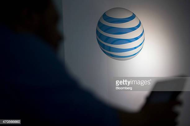 The ATT Inc logo is seen past a retail sales consultant at an ATT store in Washington DC US on Tuesday April 21 2015 ATT Inc the secondlargest US...