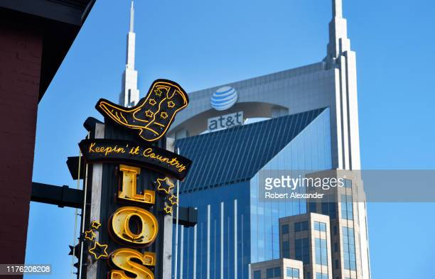 The AT&T skyscraper looms behind a neon sign over the entrance to a Nashville, Tennessee, bar and live country music venue in the city's Lower...