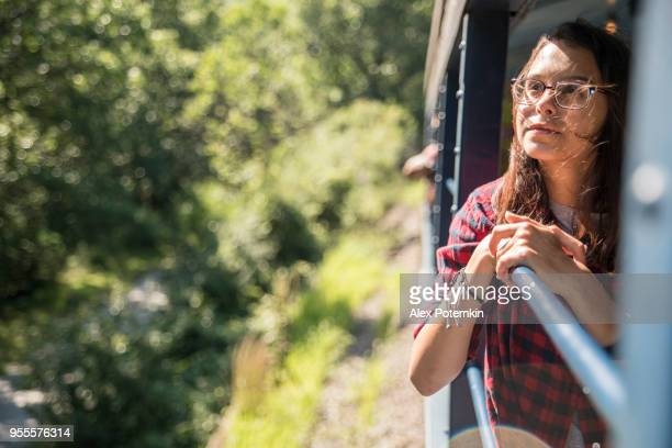 the attractive 15-years-old teenager girl enjoy the train ride through the scenic landscapes. - 16 17 years stock pictures, royalty-free photos & images