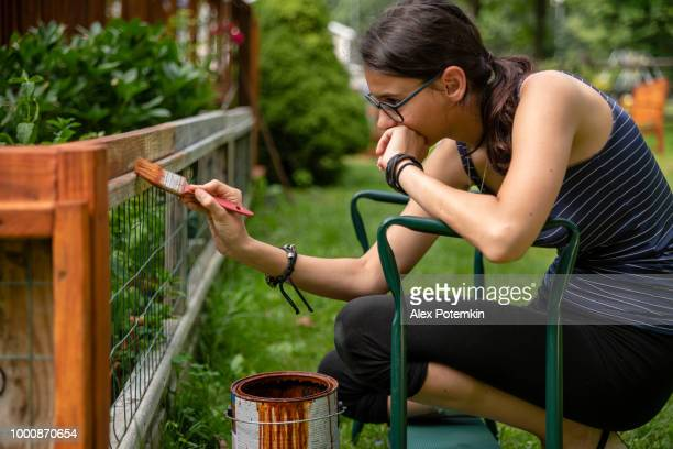 The attractive 15-years-old teenager girl painting the fence at the backyard