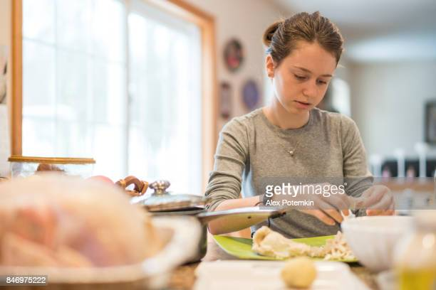 The attractive 16-years-old teenager girl helping to prepare the turkey for Thanksgiving family dinner