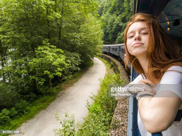 The attractive 17-years-old teenager girl enjoy the train ride through the scenic landscapes.