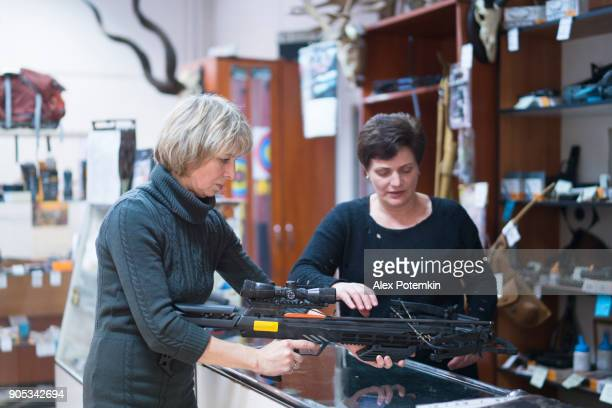 the attractive blonde mature, 50-years-old woman examining the crossbow in the small hunting store, with assistance of the woman - sales persone. - test drive stock pictures, royalty-free photos & images