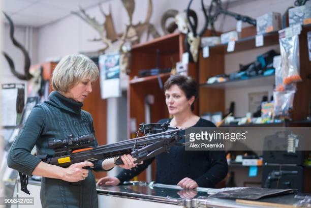 Die attraktive blonde Reife, 50 Jahre alt Frau untersuchen die Armbrust in der kleinen Jagd-Filiale mit Hilfe der Frau - Vertrieb Persone.