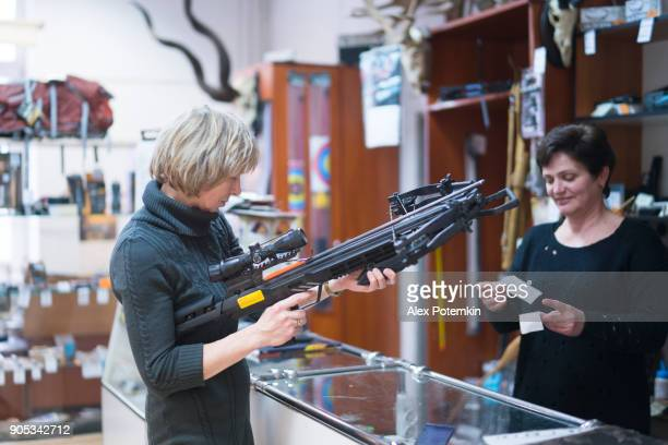 the attractive blonde mature, 50-years-old woman examining the crossbow in the small hunting store, with assistance of the woman - sales persone. - weaponry stock pictures, royalty-free photos & images