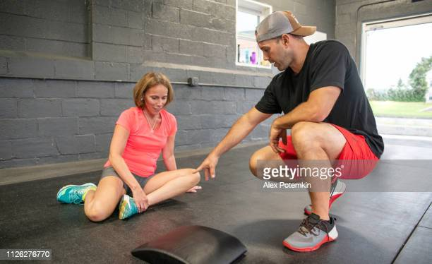 the attractive senior, 55-years-old, active latino woman doing stretching workout under the supervision of the young male coach. - alex potemkin or krakozawr latino fitness stock photos and pictures