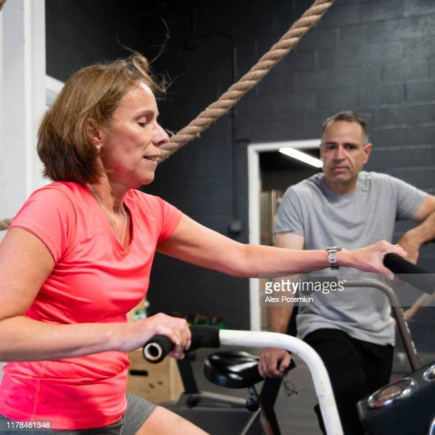 the attractive woman doing a workout on the exercise bike in the gym under the supervision of the coach, the senior 55-years-old cuban hispanic man. - 55 59 years stock pictures, royalty-free photos & images