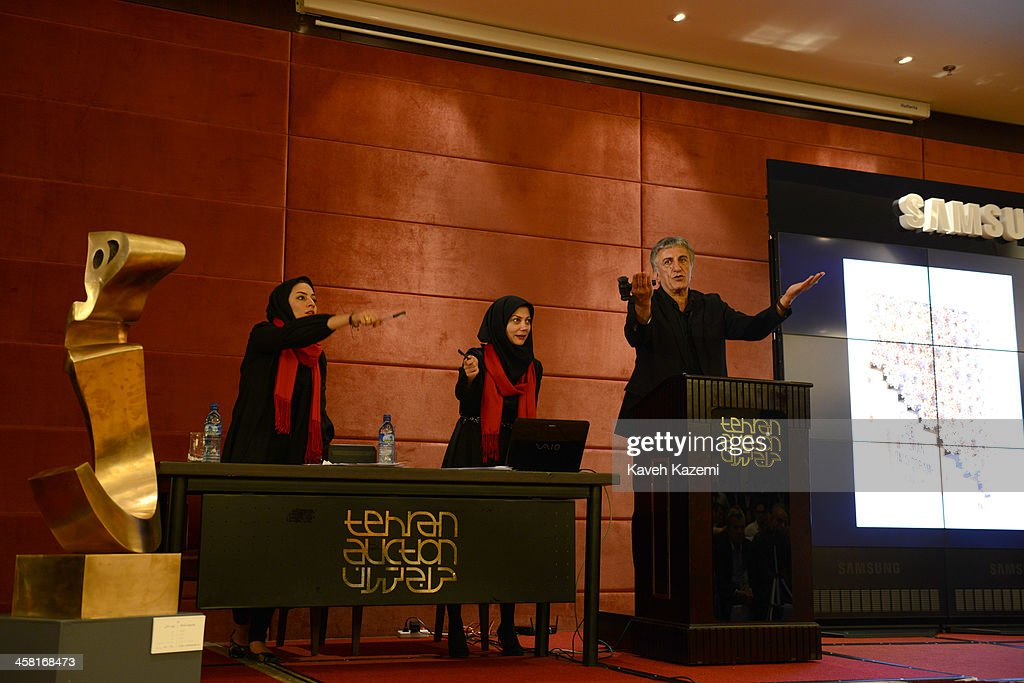 The auctioneer and veiled aids seen busy listening to the bidders during a contemporary art auction by famous Iranian artists in the dinning hall of Azadi Hotel on June 28, 2013 in Tehran, Iran.
