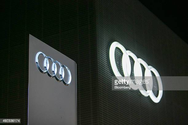 The Audi rings logo sit illuminated on the exterior of an Audi AG automobile showroom operated by Volkswagen AG at night in Berlin Germany on Sunday...