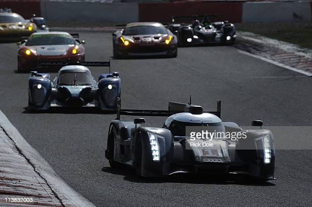 The Audi Sport Team Joest Audi R18 driven by Timo Bernhard of Germany Romain Dumas of France and Mike Rockenfeller of Germany leading a Peugeot Sport...