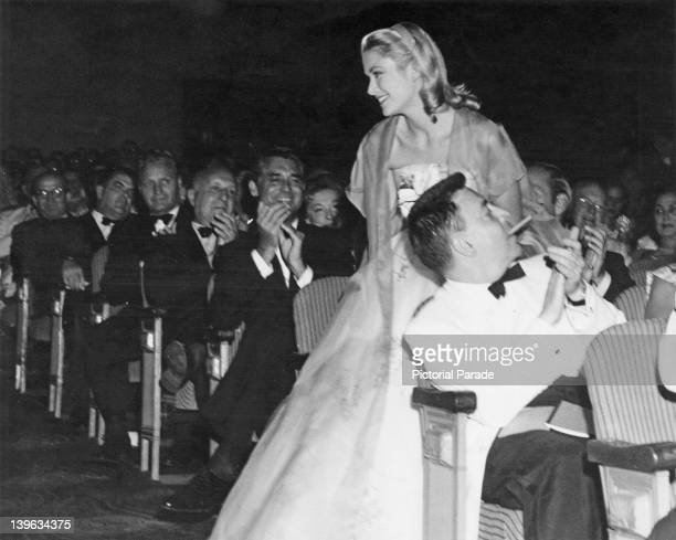 The audience applauds American actress Grace Kelly at the premiere of her latest film 'To Catch a Thief' Hollywood California 3rd August 1955 Her...
