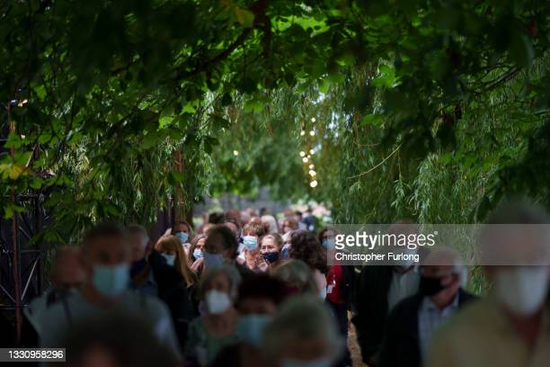 The audience brave the inclement weather as they arrive to watch the The Royal Shakespeare Company's production of The Comedy of Errors on July 27,...