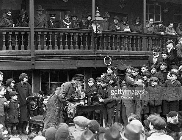 The audience watches a scene from an open air production of Dickens' Oliver Twist in the yard of the George Inn Southwark featuring Fagin Oliver...