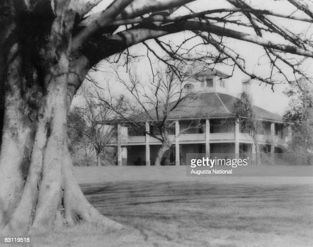 The Augusta National Golf Clubhouse is shown framed by a large oak in a general view photograph at Augusta National Golf Club in Augusta Georgia