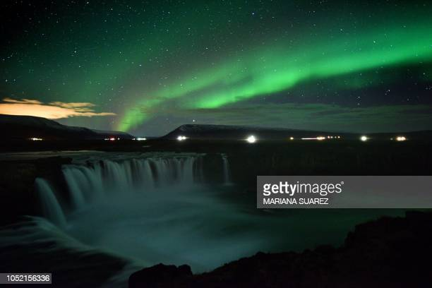 TOPSHOT The aurora borealis also known as Northern Lights is seen over Godafoss waterfall in the municipality of Thingeyjarsveit east of Akureyri in...