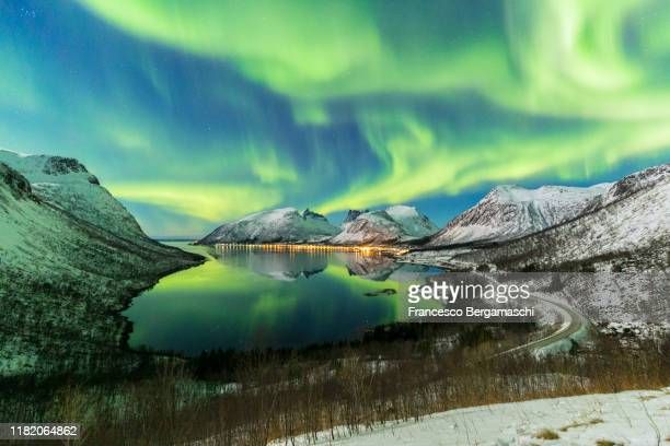 the aurora borealis lights up in the sky and is reflected in the fjord. northern norway, europe. - norway stock pictures, royalty-free photos & images