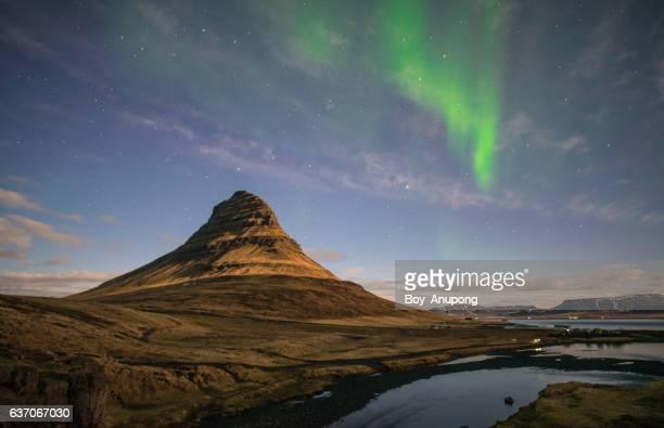 The Aurora borealis over Kirkjufell mountain the iconic landmark mountain in West Iceland.