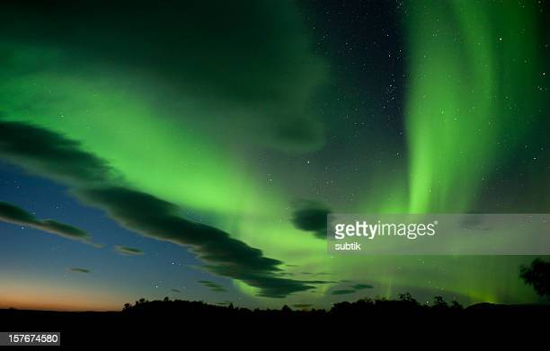 The aurora borealis paints the  night sky with green