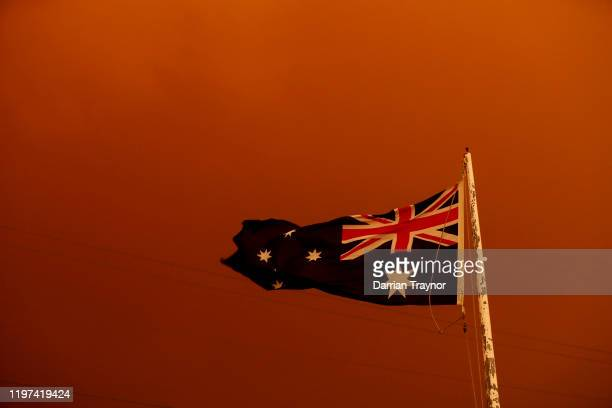 The Australia Flag flies under red skies from the fires on January 04 2020 in Bruthen Australia Two people are dead and 28 remain missing following...