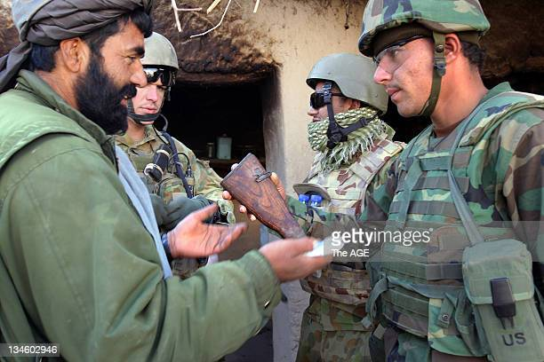 The Australian and Afghan National Army search a village at Musazai in the Uruzgan Province in Afghanistan. Soldiers question a man where a rifle...