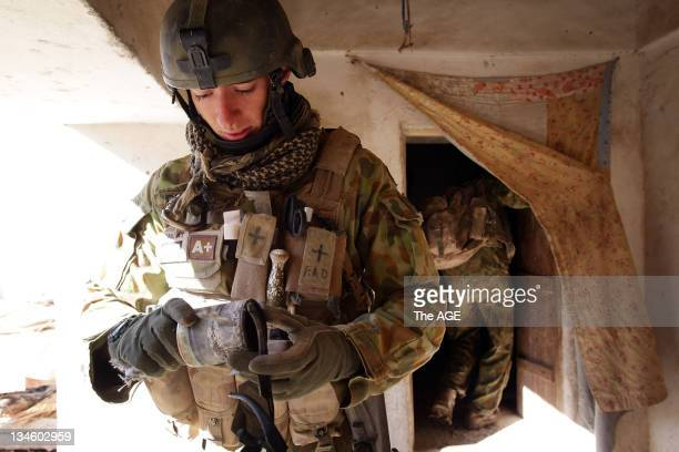 The Australian and Afghan National Army search a village at Musazai in the Uruzgan Province in Afghanistan Sapper Matthew Dellosa inspects a...