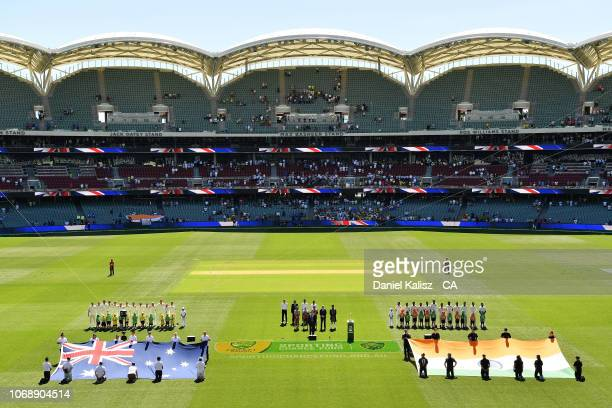The Australian and Indian teams pause for their national anthems during day one of the First Test match in the series between Australia and India at...