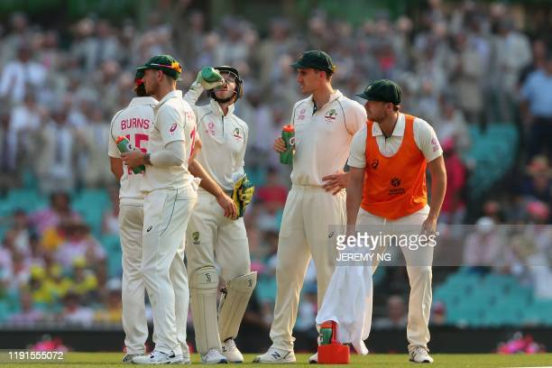 The Australian cricket team rehydrates in sweltering heat late in the second day of the third cricket Test match between Australia and New Zealand at...
