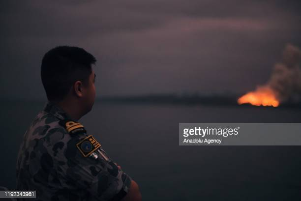 The Australian Department of Defence shows a fire in the distance seen from the Royal Australian Navy's HMAS Adelaide ship off the coast in Eden in...