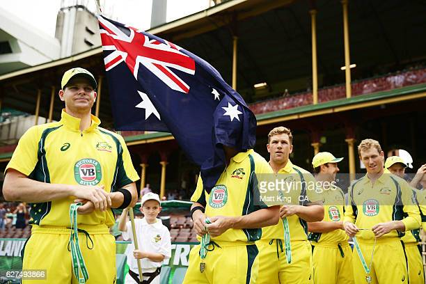 The Australian flag blows over the face of David Warner of Australia as Steve Smith of Australia looks on during game one of the One Day...