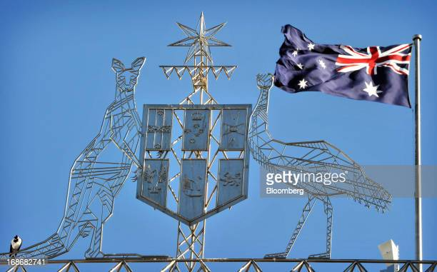 The Australian flag flies behind the coat of arms of Australia above Parliament House in Canberra Australia on Tuesday May 14 2013 Today's federal...
