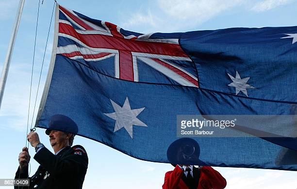 The Australian flag is lowered as a bugler plays The Last Post during the Anzac Day meeting at Flemington Racecourse on April 25 2009 in Melbourne...