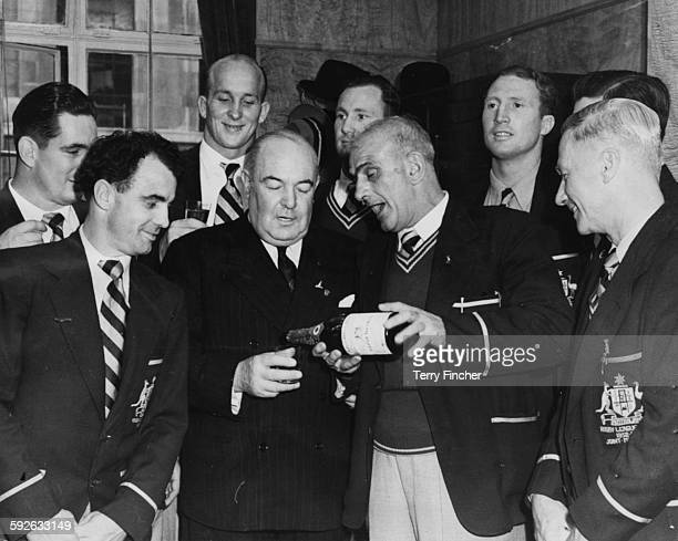 The Australian Kangaroos Rugby League team watching as manager Norman Robinson pouring a glass of champagne for AgentGeneral J M Tulley including...