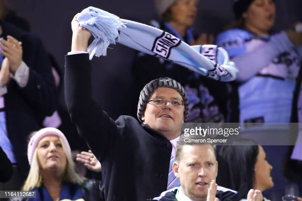 The Australian Prime Minister, Scott Morrison enjoys the atmosphere during the round 19 NRL match between the Cronulla Sharks and the North...