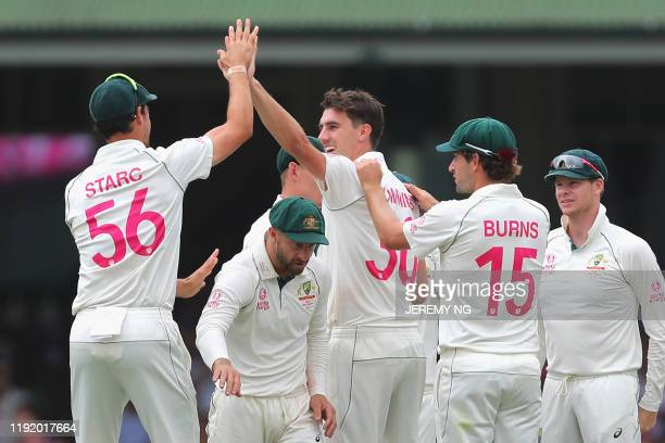 The Australian team and Pat Cummins celebrate the wicket of New Zealand's Ross Taylor during the fourth day of the third cricket Test match between...
