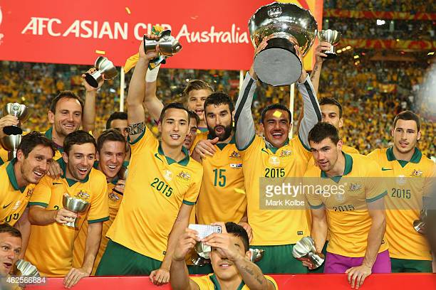 The Australian team celebrate with the trophy as Massimo Luongo of Australia takes a selfie during the 2015 Asian Cup final match between Korea...