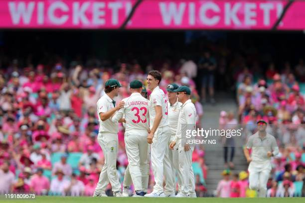 The Australian team celebrates the wicket of New Zealand's captain Tom Latham during the third day of the third cricket Test match between Australia...