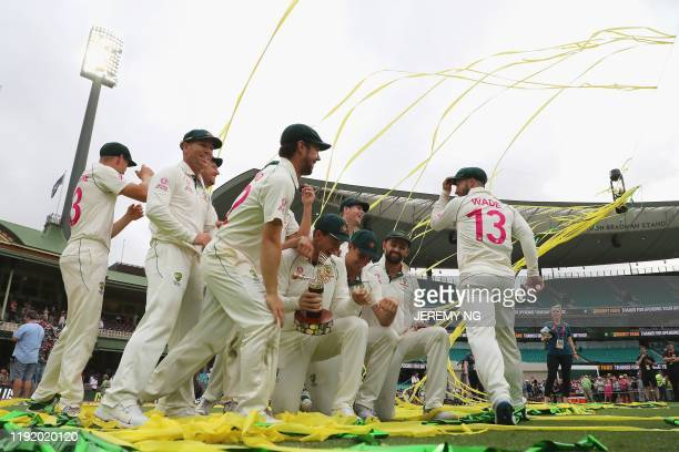 The Australian team celebrates with the TransTasman Trophy after winning the series on the fourth day of the third cricket Test match between...