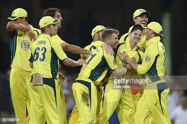 The Australian team congratulate Steven Smith after he took the catch to dismiss BJ Watling of New Zealand during game one of the One Day...