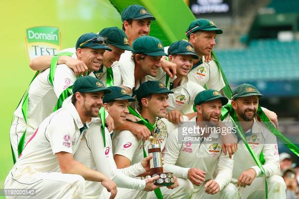 The Australian team poses with the TransTasman Trophy after winning the series on the fourth day of the third cricket Test match between Australia...