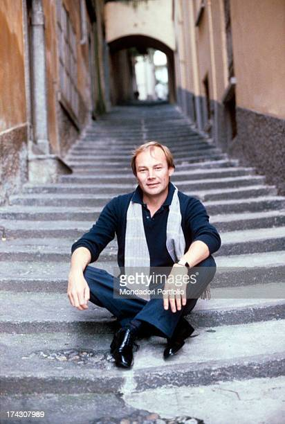 The Austrian actor Klaus Maria Brandauer histrionic performer of various manysided roles sits relaxed on a flight of steps Italy 1982