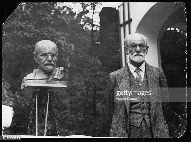 The Austrian psychiatrist and founder of the theory of psychoanalysis Sigmund Freud stands beside a sculpture of himself