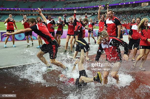 The Austrian team celebrate by dunking a member of coaching staff in the water jump following their silver medal in the Athletics Team Championship...