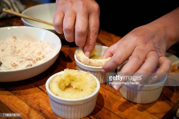 The author forms bread into a small baking dish while making Roasted Applesauce Charlottes using heirloom apples, for Green Plate Special,...