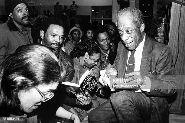 The author James Baldwin sitting and signing books in a crowded book store, 1980.