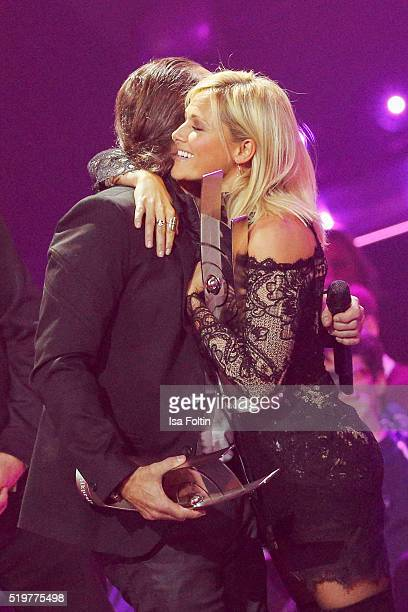 The award winners Alex Christensen and Helene Fischer embrace each other on stage during the Echo Award 2016 show on April 07 2016 in Berlin Germany